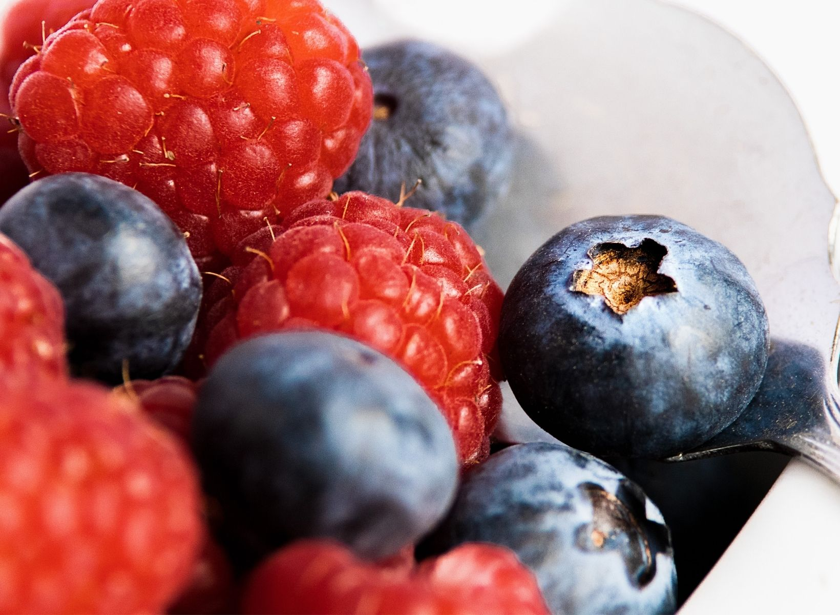 Close up shot of raspberries and blueberries in a bowl with a spoon