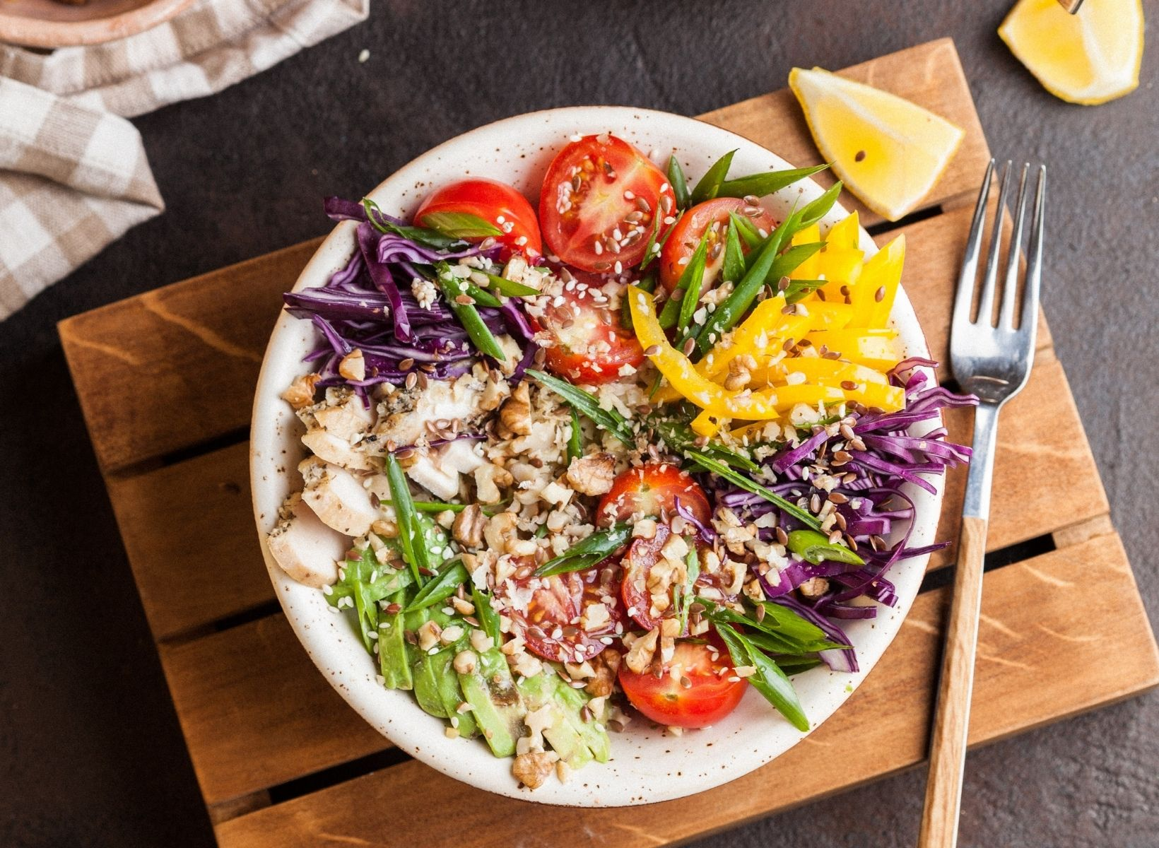 A white bowl filled with low-glycemic vegetables is sitting on a wood cutting board next to a fork and slices of lemon