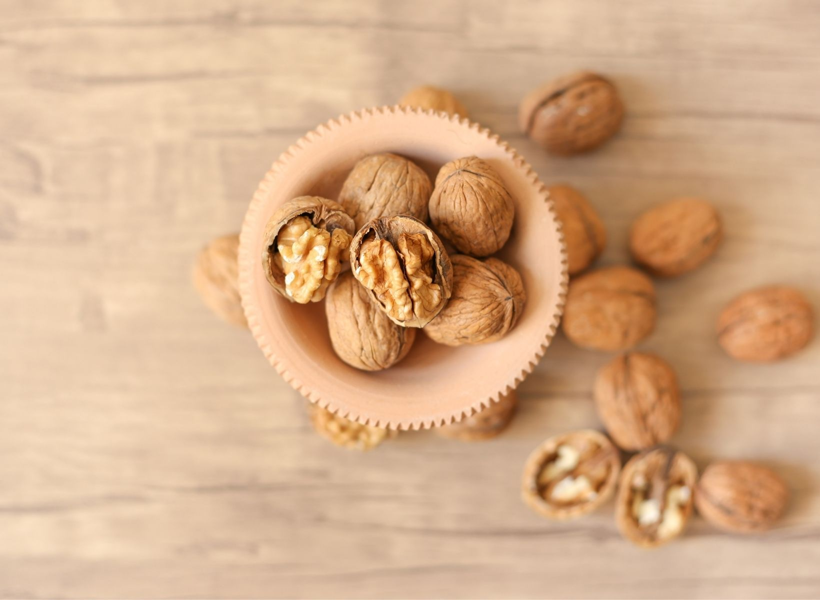 An overhead shot of a small brown bowl with walnuts, an example of a low-glycemic snack