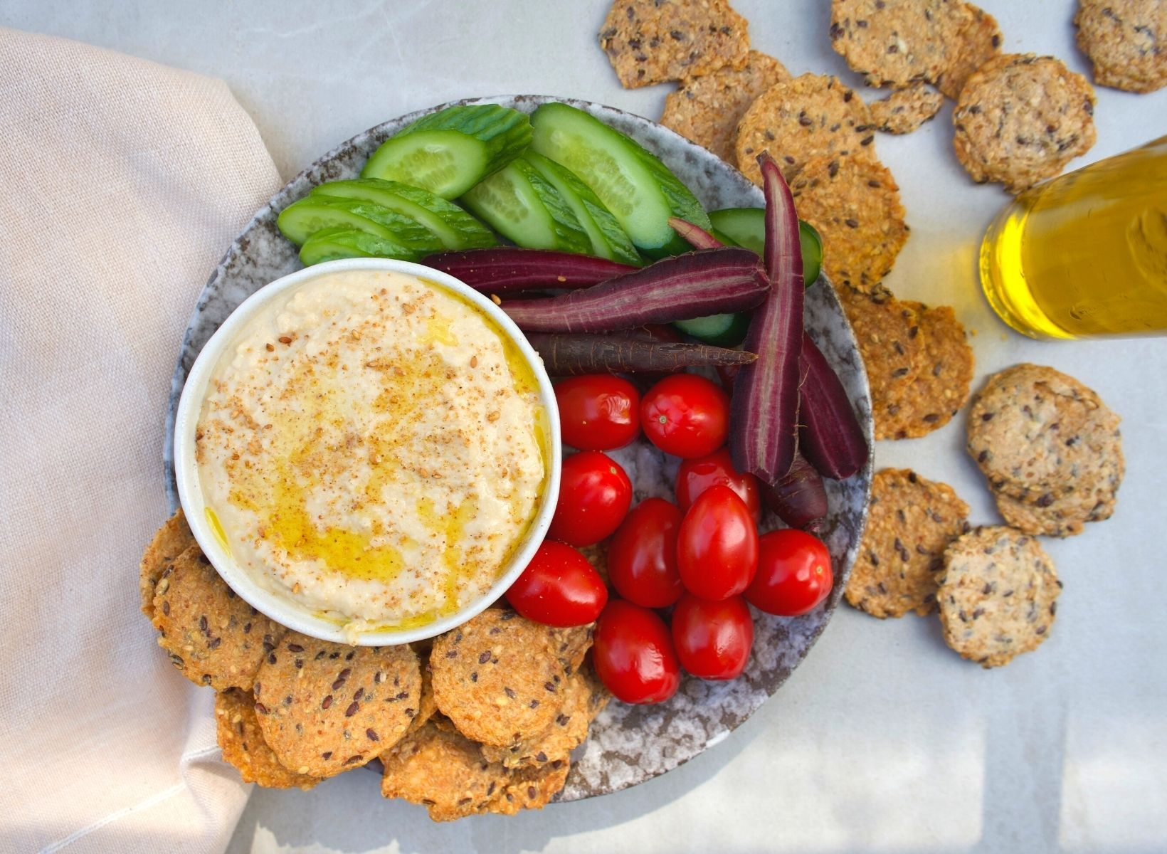 Overhead shot of a white bowl of hummus, a low-glycemic snack. A plate with sliced cucumbers, cherry tomatoes, purple carrots, and whole grain crackers are on the side