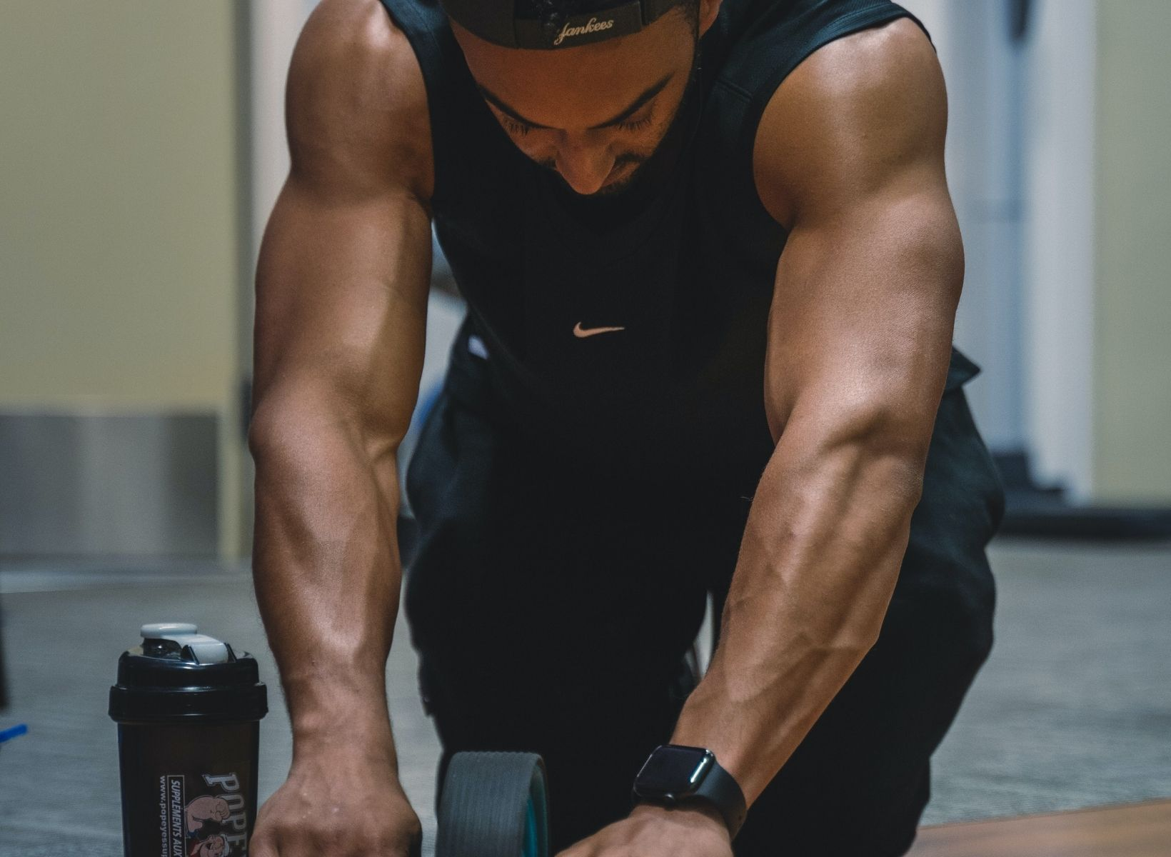 A man using an ab roller to work his core; next to him is a protein shake