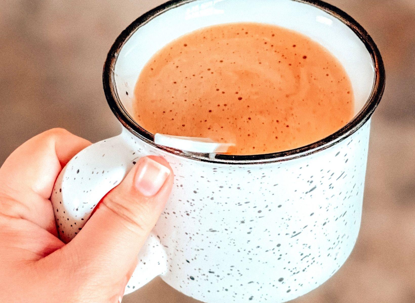 A closeup shot of a hand holding a white mug with keto coffee inside