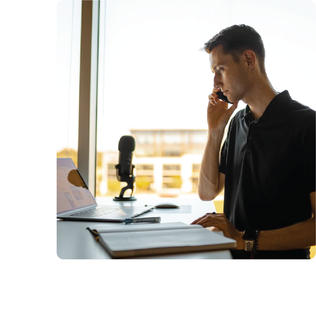 an individual working from a desk and making a phone call