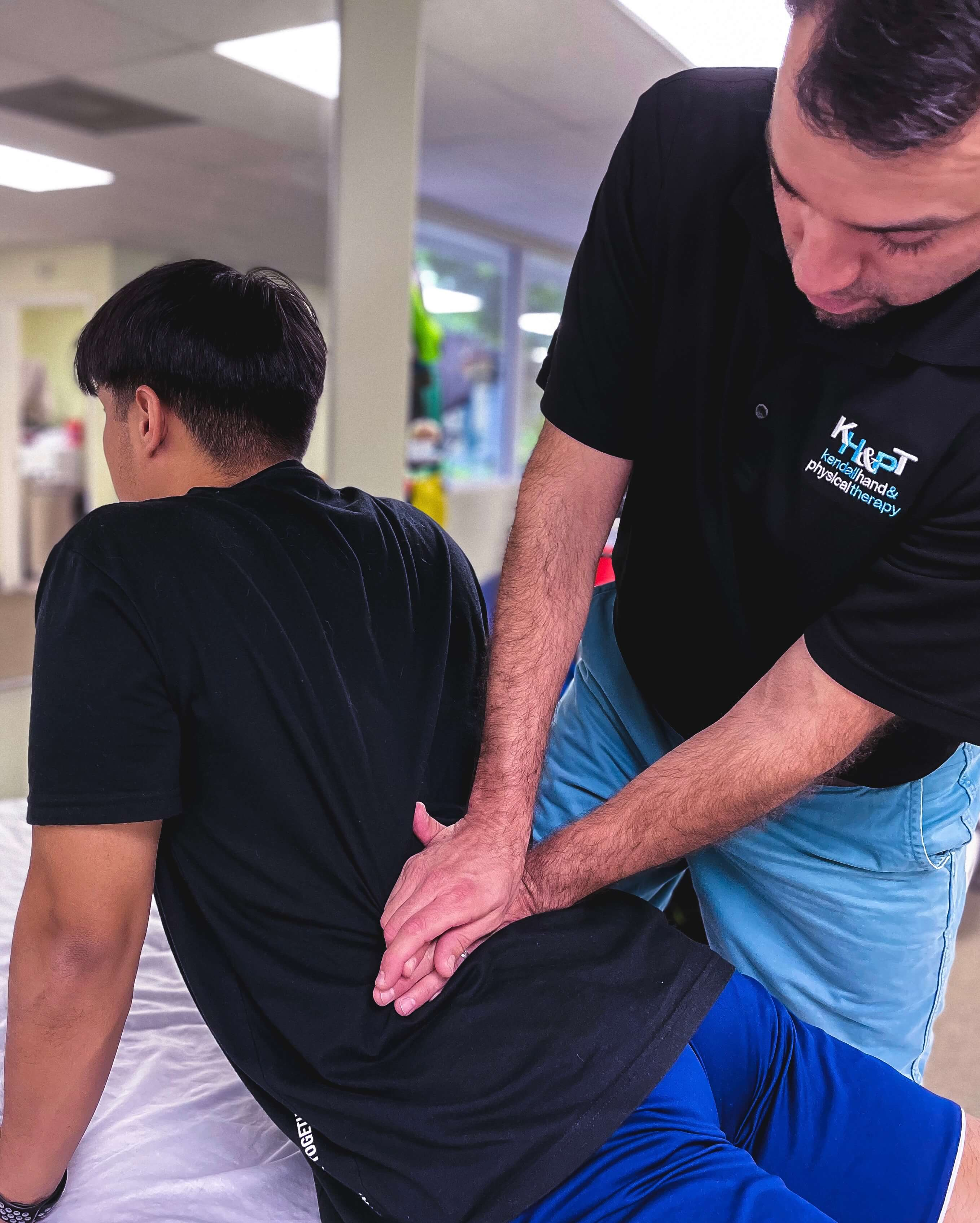Therapist helps a man rehab his lower back