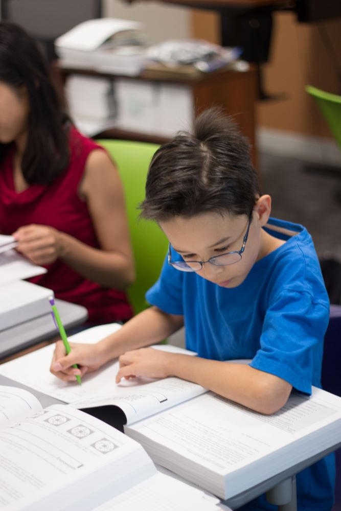 boy-in-blue-shirt-writing-in-book