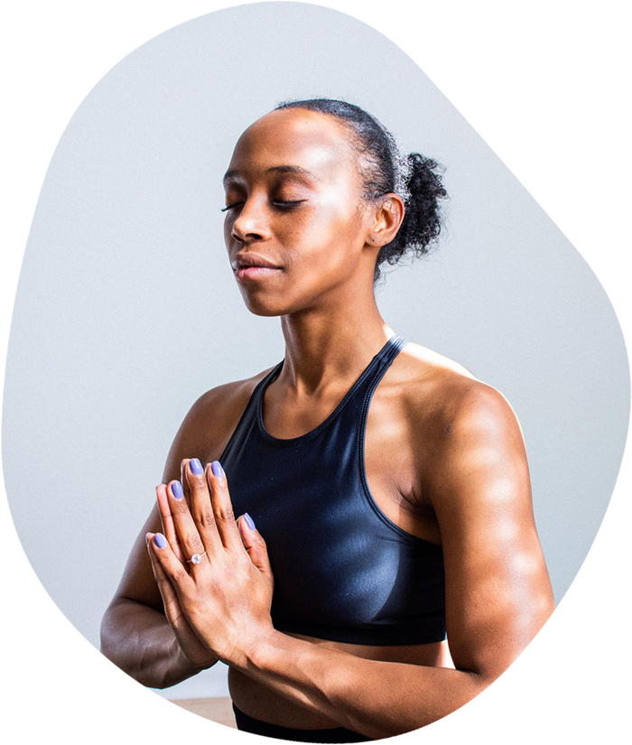 A woman in yoga attire meditating with prayer hands in front of her chest