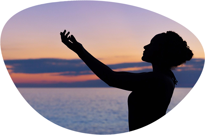 The silhouette of a woman with her arms lifted, a sunset in the background