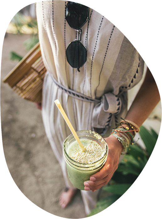 A woman dressed in white holding a green juice with a straw
