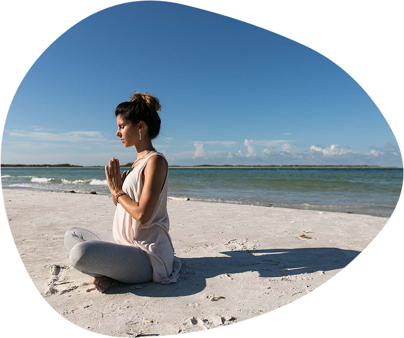 A woman meditating with prayer hands in front of a beach