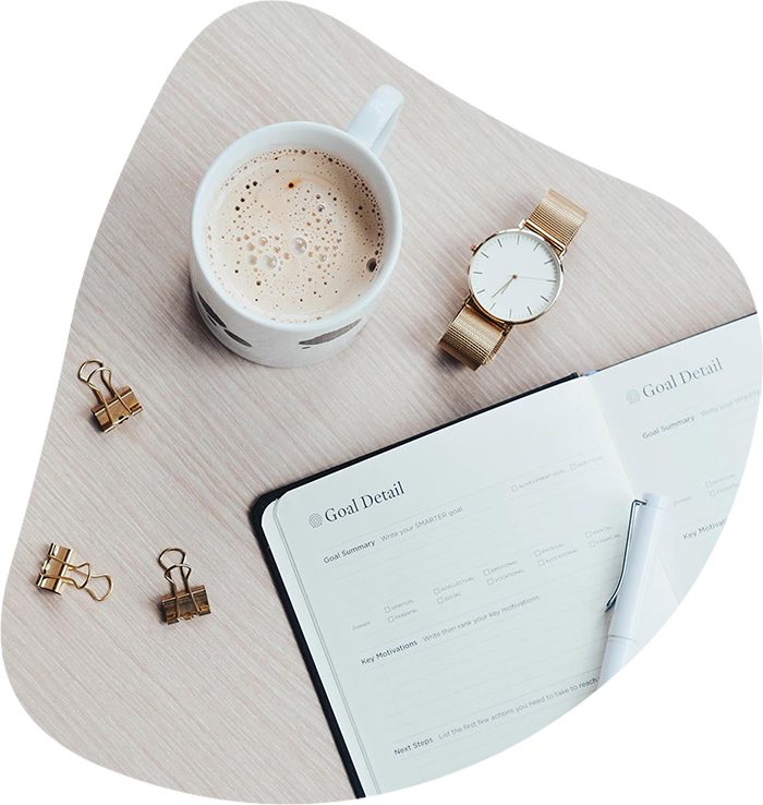 Top view of a desk with a goal planner, coffee, and a golden watch