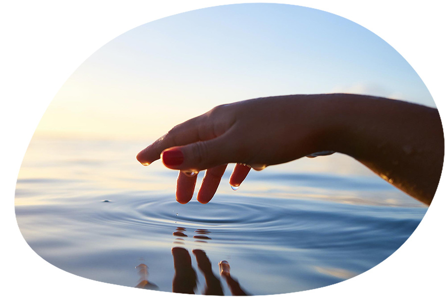 A hand gently reaching out toward the water