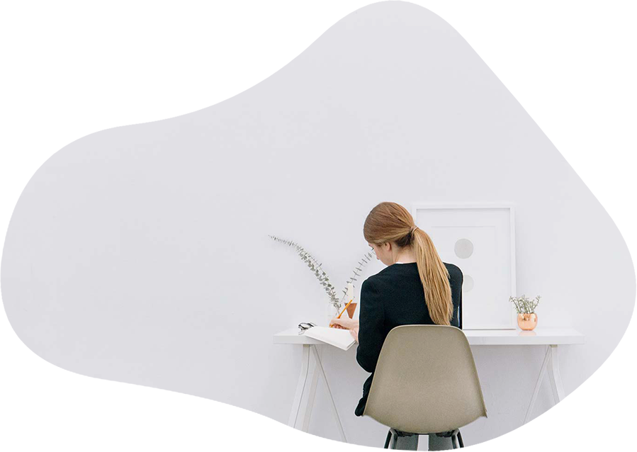 A woman sitting in front of a desk with a white background