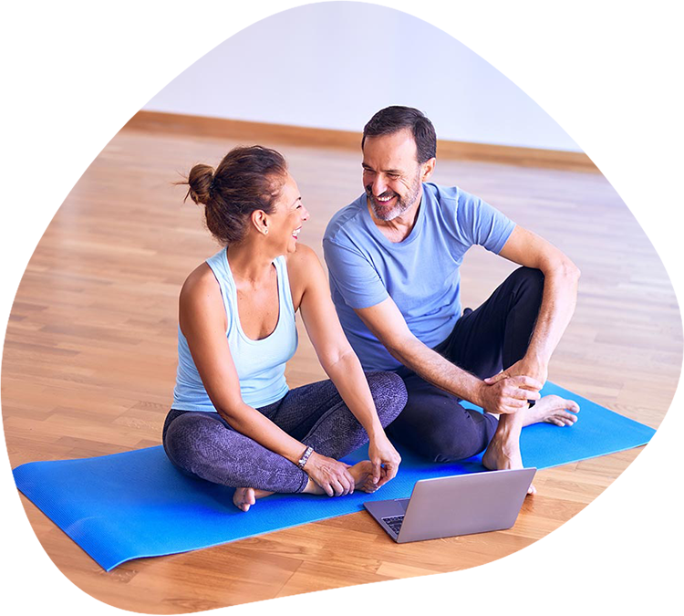 Two people on a yoga mat, smiling at each other, with a laptop in front of them