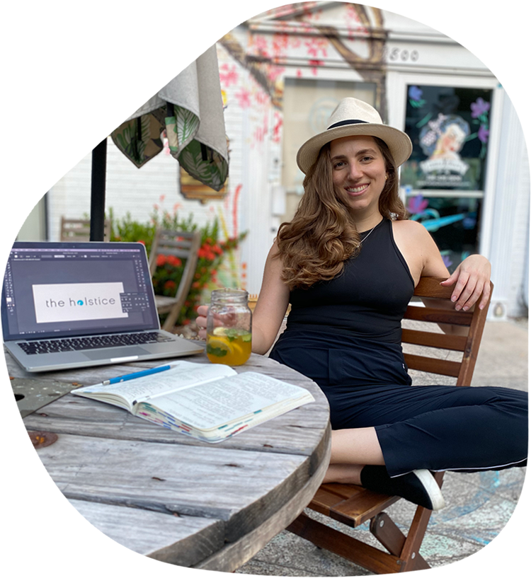 Nicole wearing a straw hat sitting in front of a wooden table with her laptop and notebook open