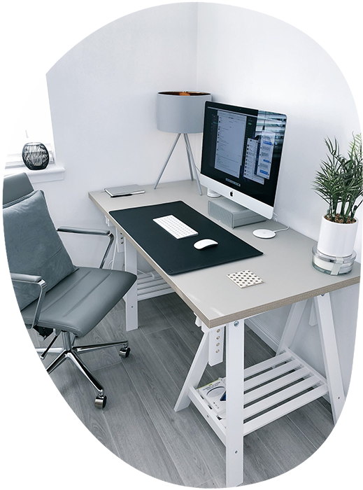 A white desk with a large computer, lamp, and plant, and a gray chair in front of it.