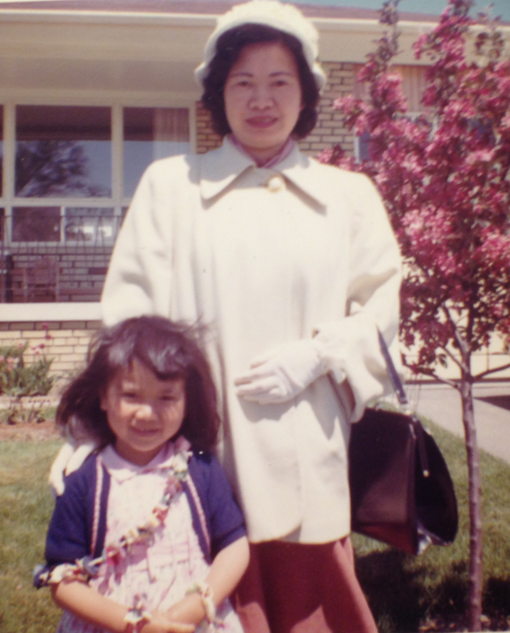 Brenda Joy Lem as a small girl posing in front of a house with her mother, a tree is flowering in the background