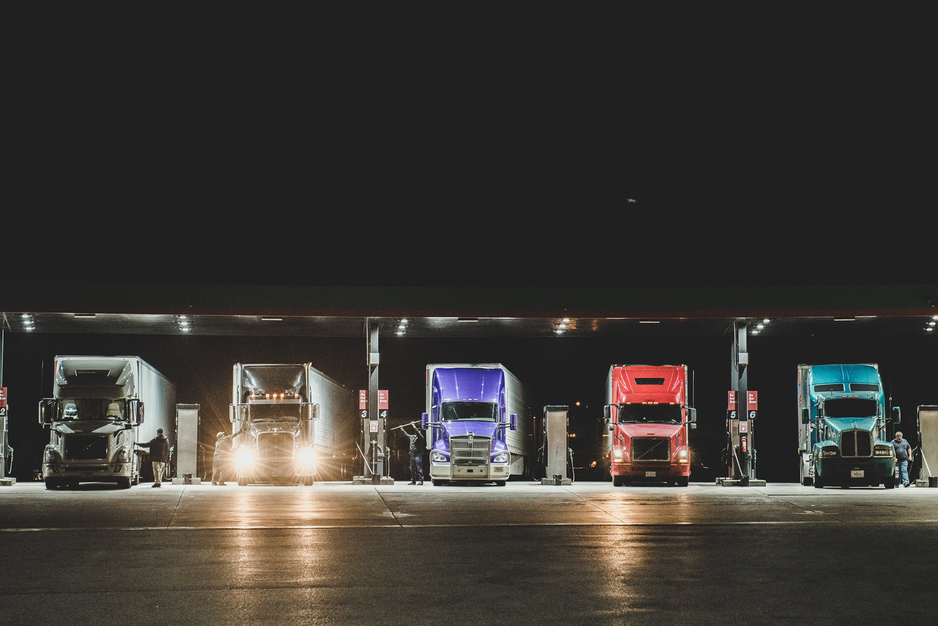 A row of trucks at a gas station. One truck has its headlights on.