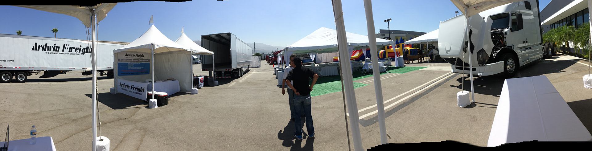 A panoramic photo of trucks on a lot at an event.