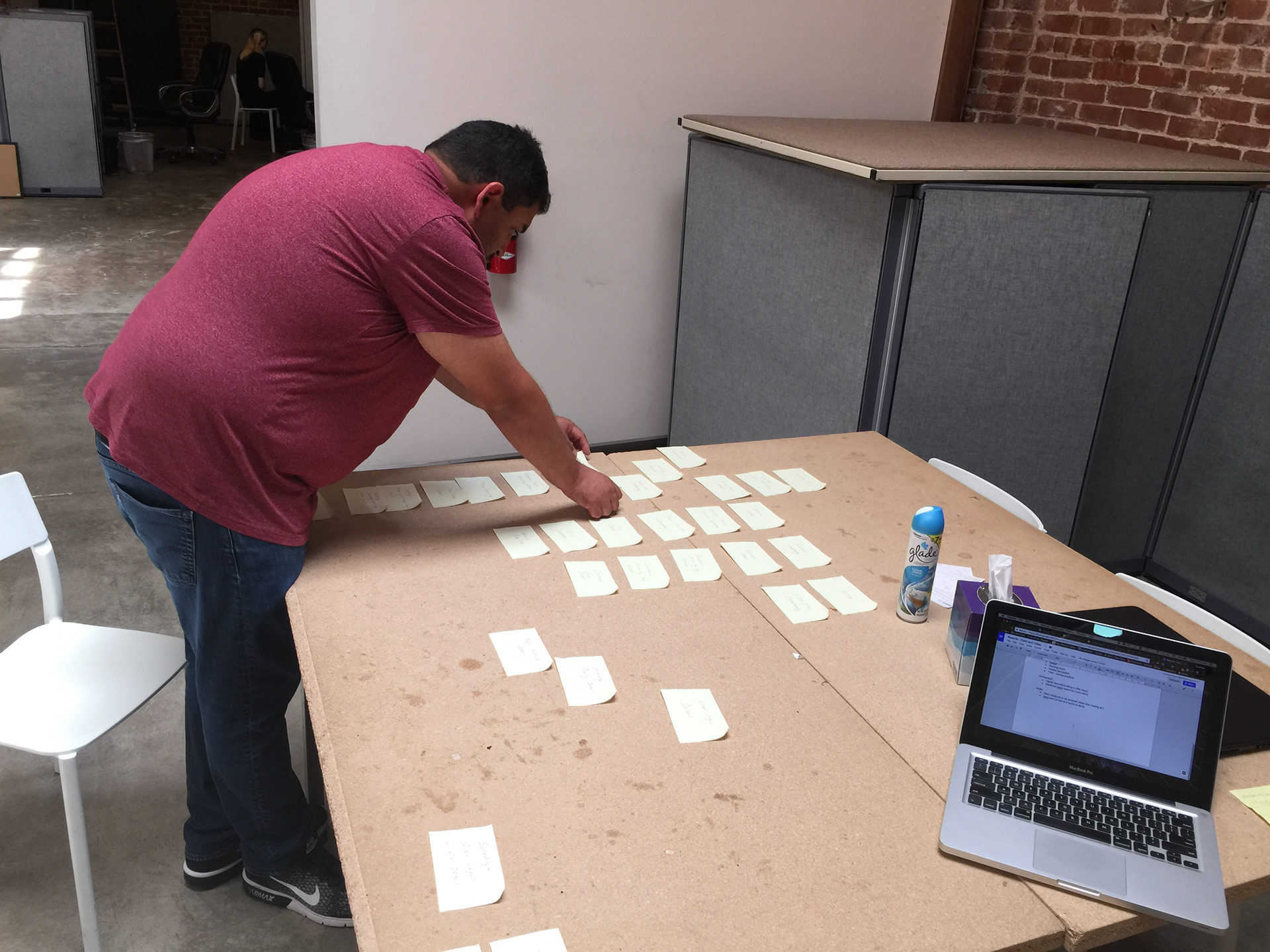 A man sorting post-it notes on a table.