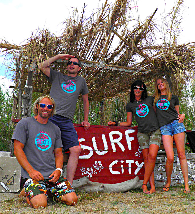 Modells an Strandbar tragen T-Shirts mit Surf-Druckmotiv