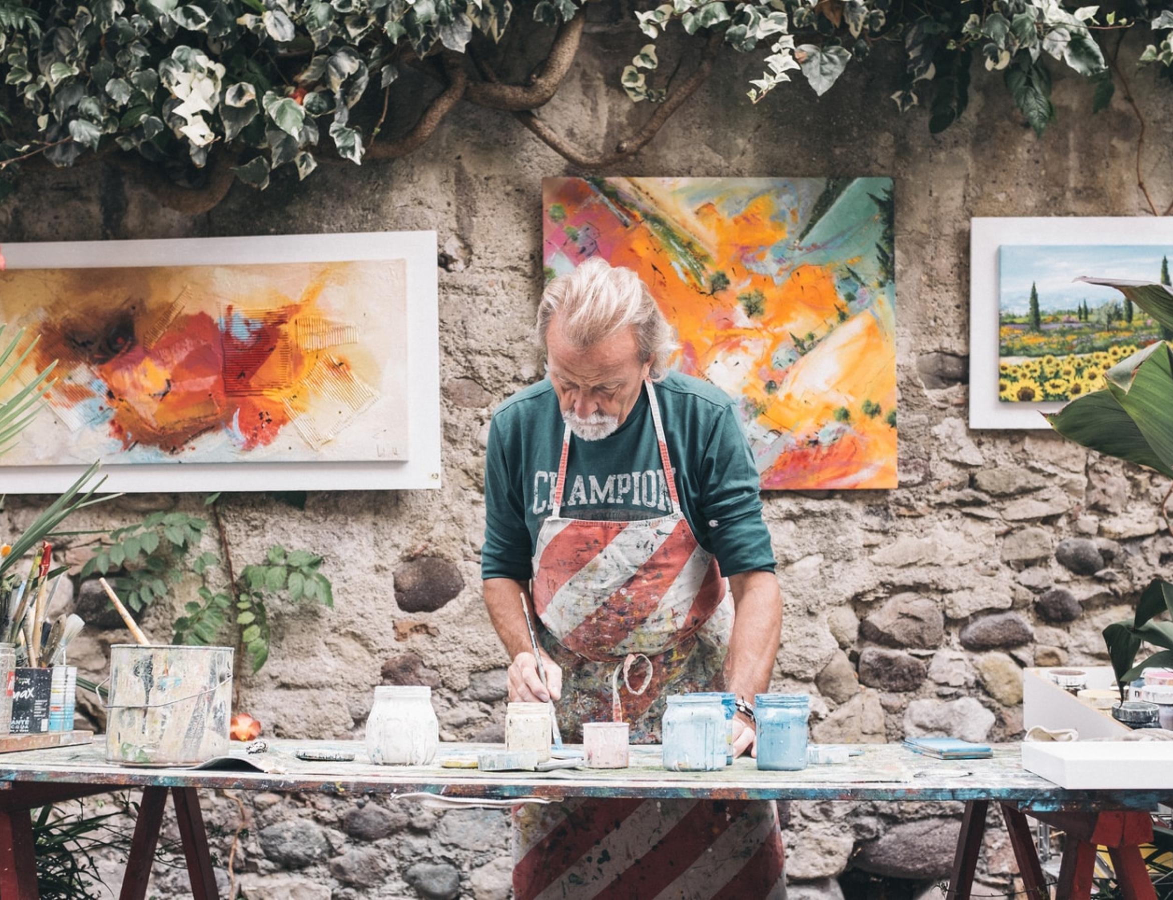 Older man painting in outdoor studio