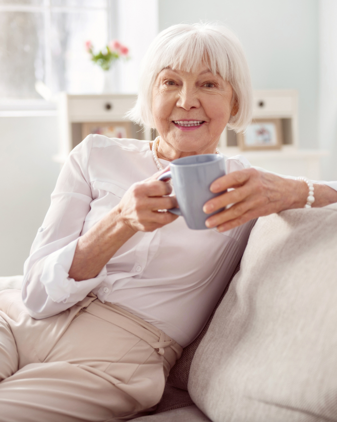 Older woman on couch with coffee cup