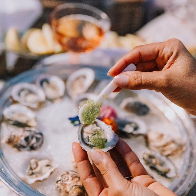 Oysters with toppings being added