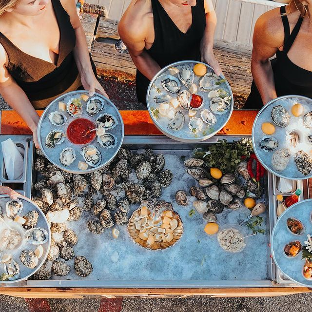 Shucked roaming servers with oysters trays
