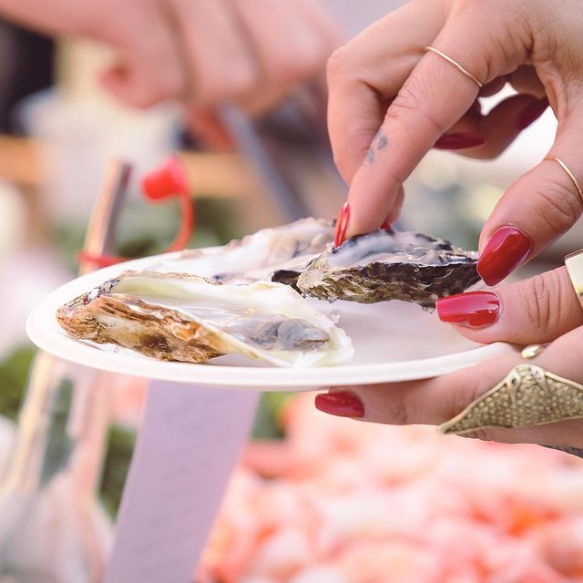 Close up of person grabbing freshly shucked oysters