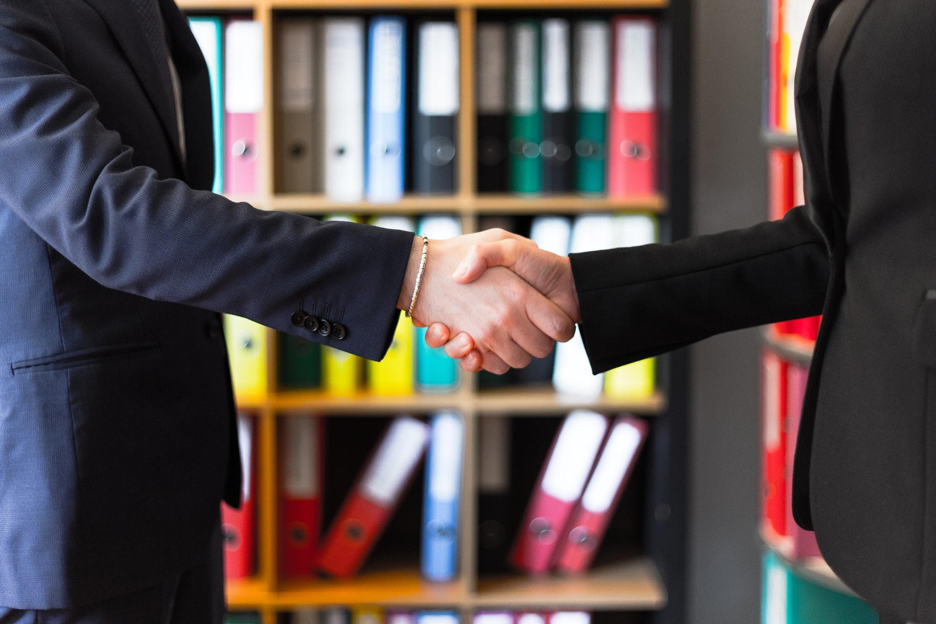 Zwei Mitarbeiter die sich die Hände schütteln nach übernahme