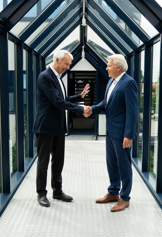 Forum Geschäftsführer Burkhard Wittek und Mittelständlicher Unternehmer schütteln Hände nach der Unternehmensübernahme