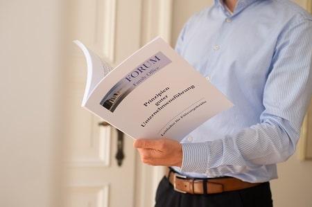 Forum Family Office Mitarbeiter beim Lesen von Prinzipien guter Unternehmensführung im Falle einer Beteiligung