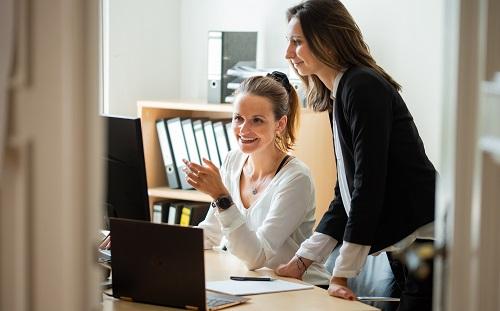 Zwei Forum Mitarbeiter die sich gegenseitig bei der Arbeit helfen