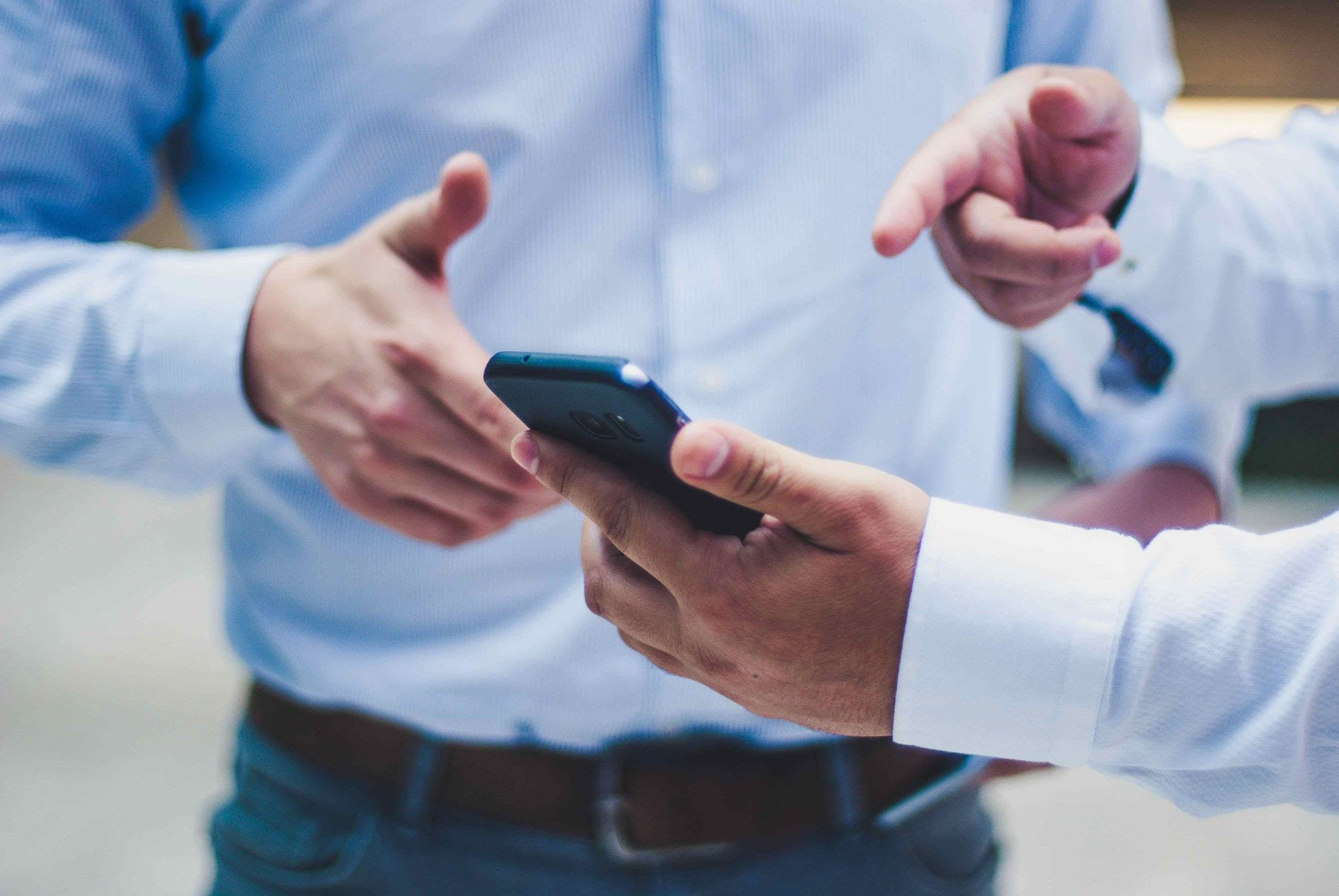Two men in business clothes point at a smartphone