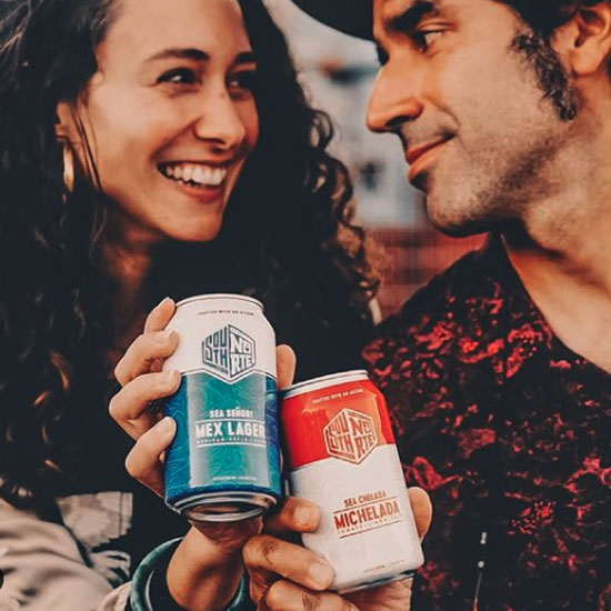 A man and a woman toasting cans of SouthNorte