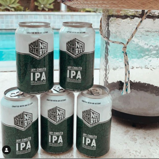 five Ay Cheilita cans stacked on a table by a pool