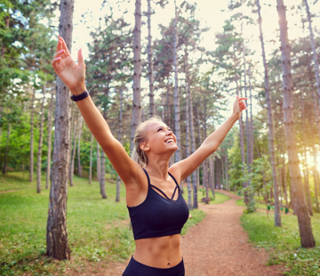 A blonde woman standing in the forest on a path with the sun shining. She's wearing a cropped athletic tank and is looking and smiling at the sky with her arms raised in a V-shape.
