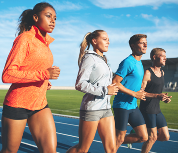 People in athletic gear shirts and shorts running on a track during a nice sunny day.