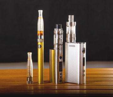 Various vape pens sitting upright on a wooden table with a black background.