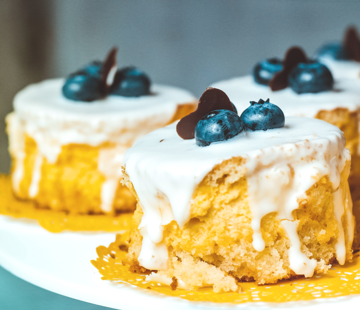 A plate of three baked mini cakes drizzled with white frosting cream and topped with three blueberries each.