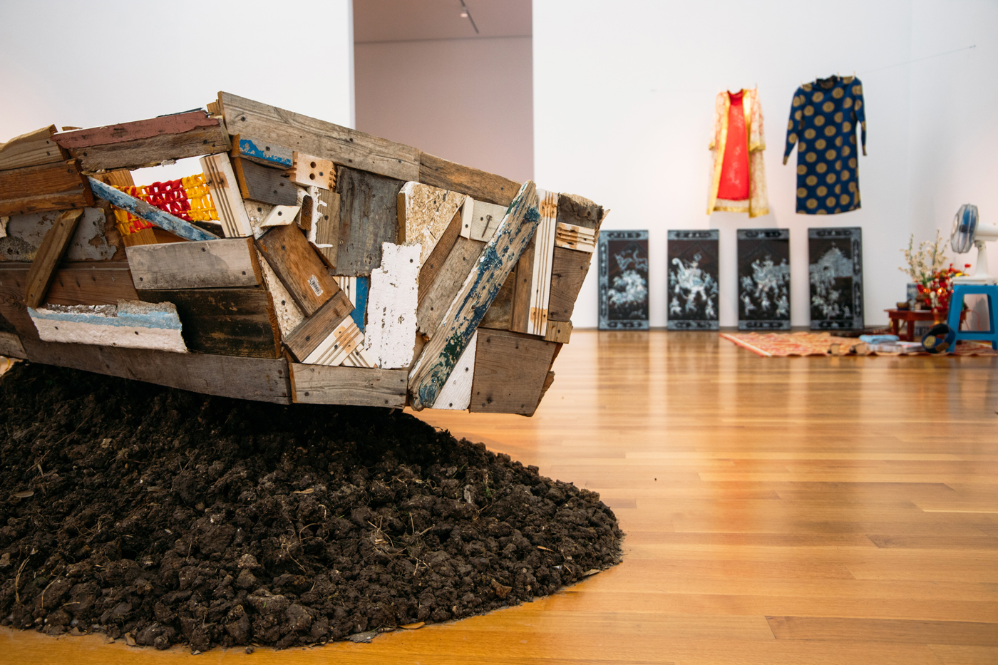 Image of an installation by Brandon Tho Harris containing a boat sculpture in the foreground and other sculptural objects in the background.