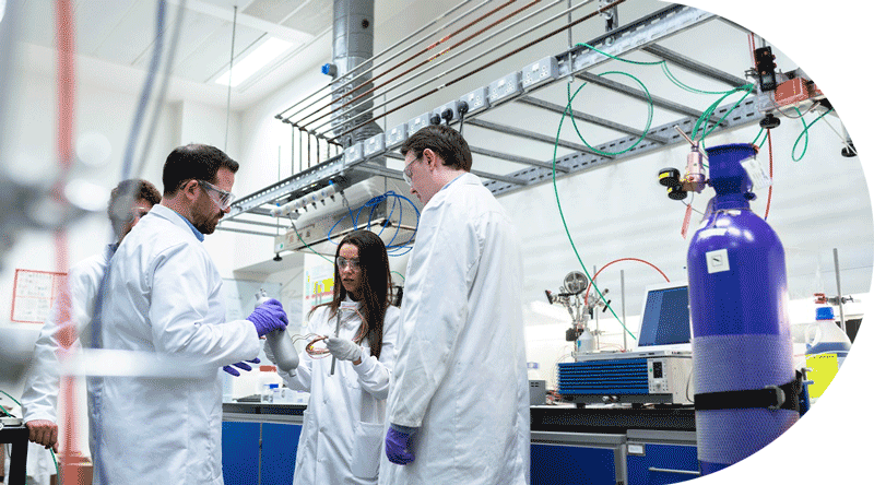 Four scientist in a laboratory discussing the work