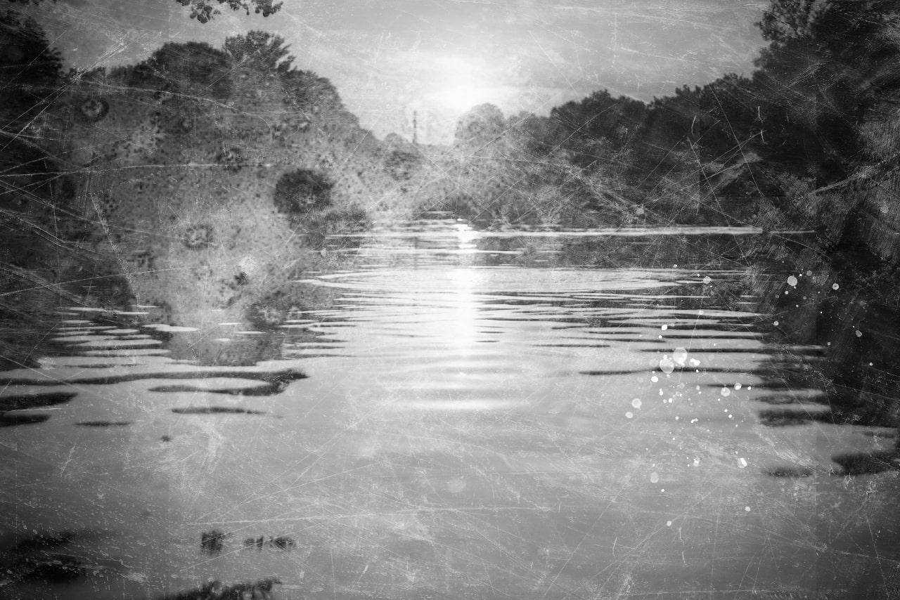 à gauche, une photo en noir et blanc d'une vue sur le Karpfenteich. On peut voir la surface de l'eau et les arbres environnants. La photo semble être rayée et avoir des taches d'eau, comme une vieille photo sur papier.