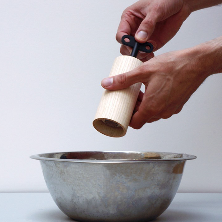 Hands holding a pepper mill being using