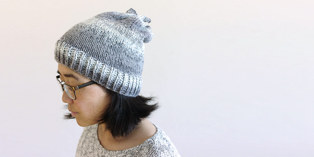 Photo of Tami looking down wearing a hat she knit.