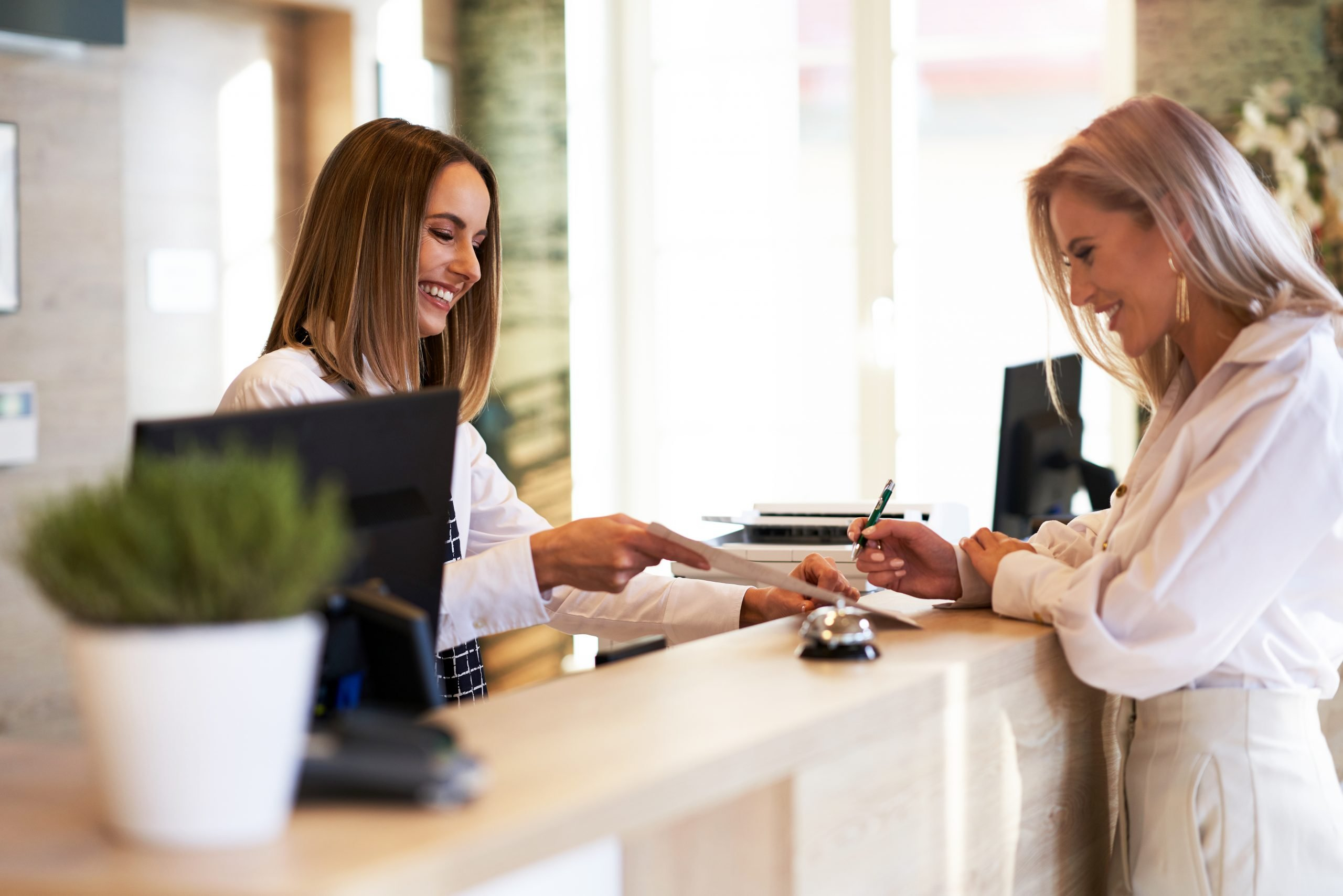 Picture of receptionist and businesswoman at hotel front desk.