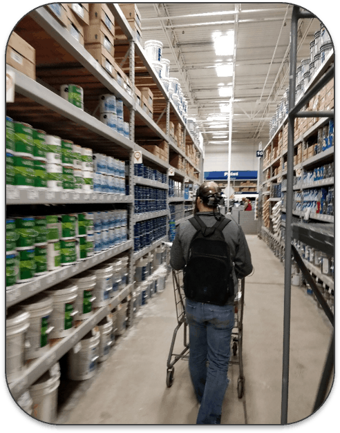 A man with eye tracking equipment attached to his headwalking down a supermarket aisle.