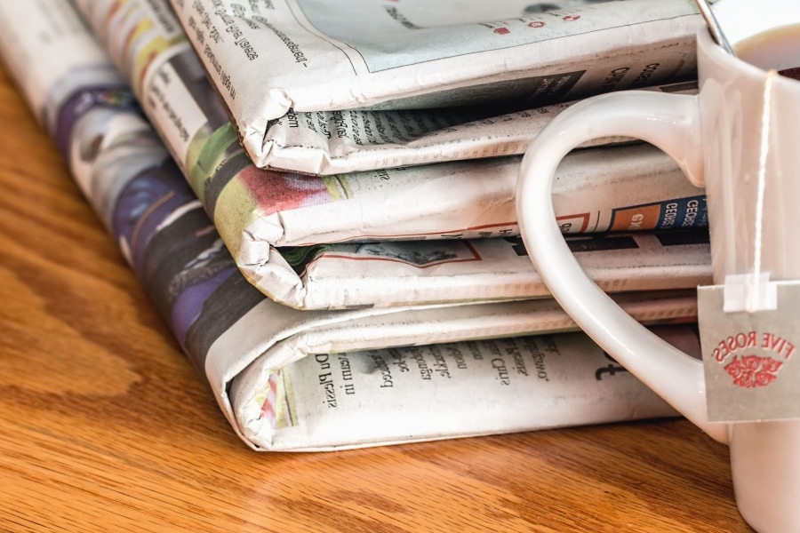 Three newspapers stacked next to each other next to a mug of tea.