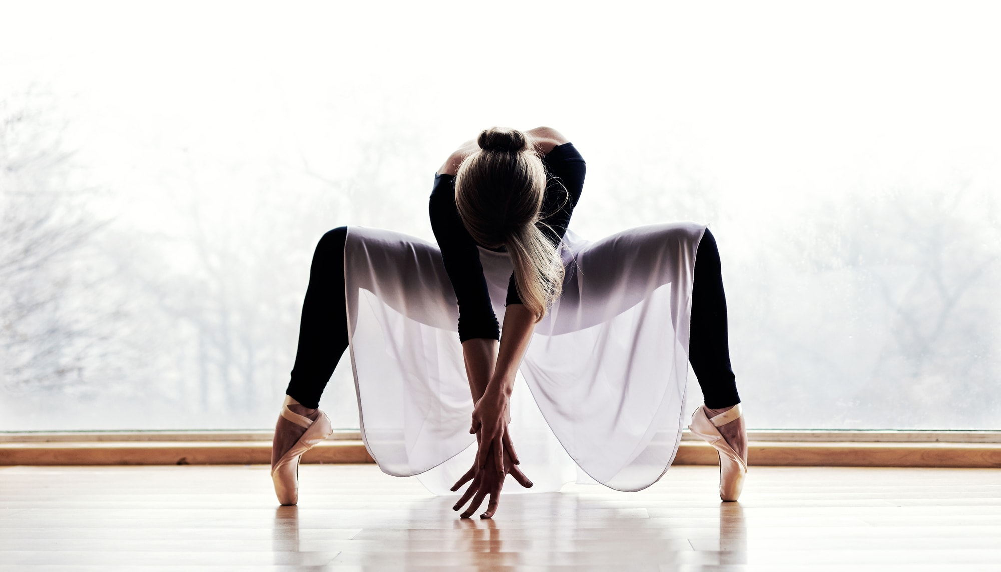 A ballerina crouching low on pointe.