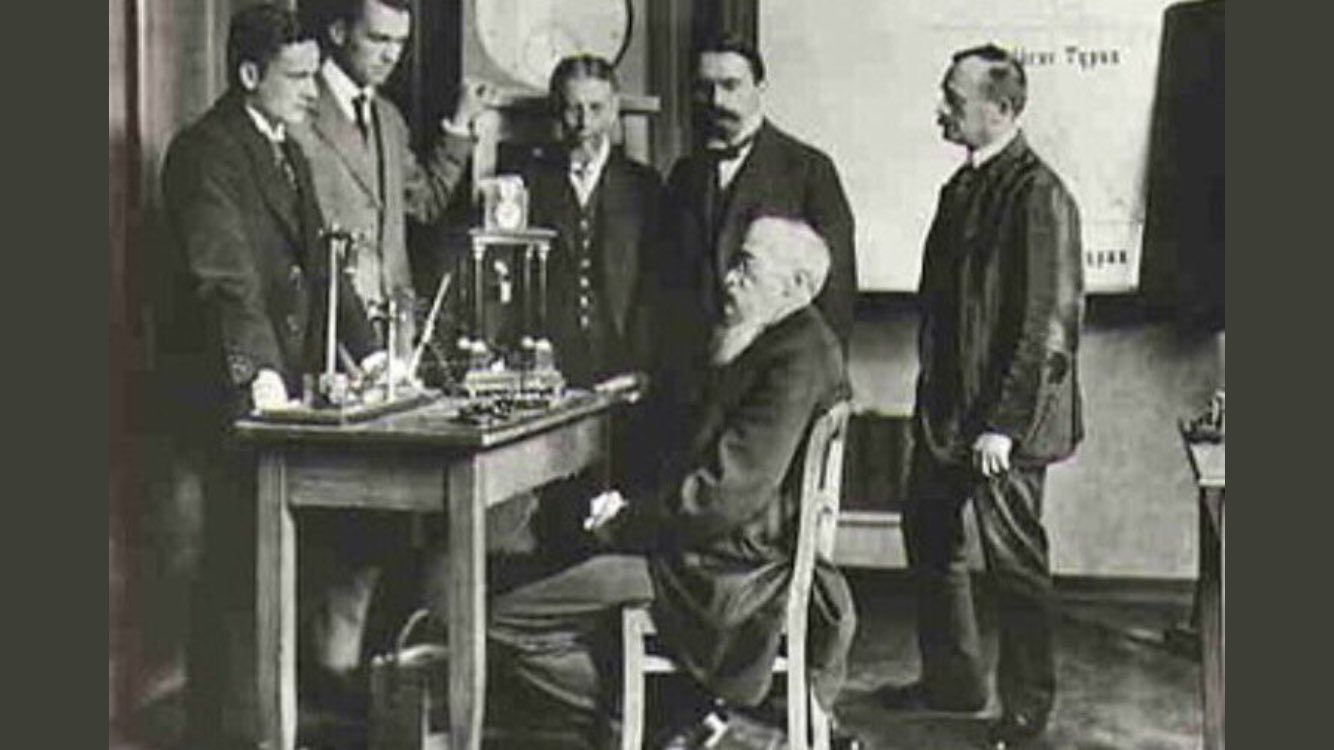 Wilhelm Wundt seated at his desk with 5 peers surrounding him.